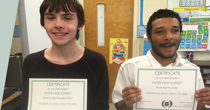 Two students holding certificates for passing a test on interviewing.